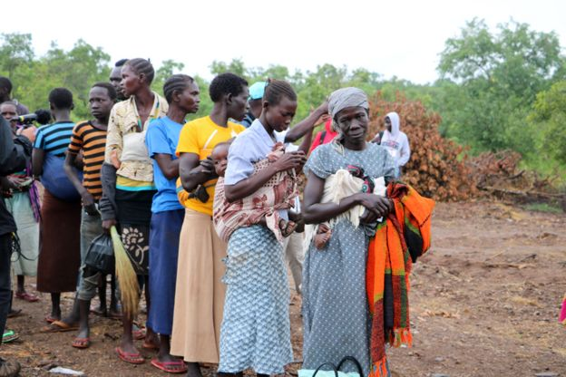 A line of women wait to be shown where they will be living