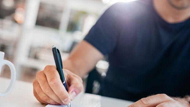 Un hombre escribiendo en un diario