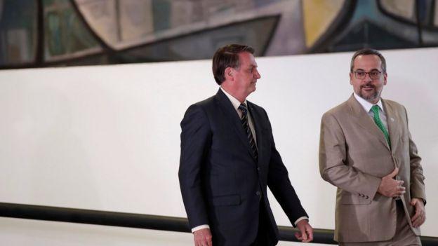 Jair Bolsonaro e de Abraham Weintraub sorriem enquanto conversam e descem rampa no Palácio do Planalto