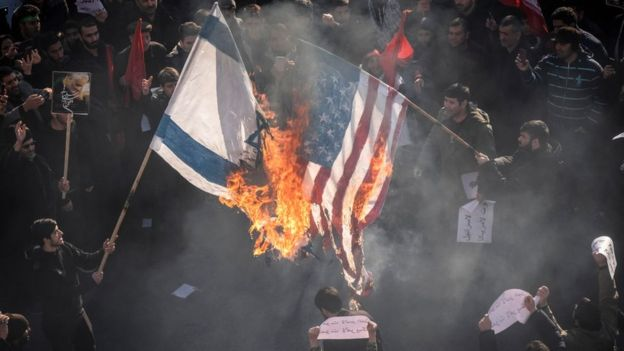 Banderas de EE.UU. e Israel en fuego.