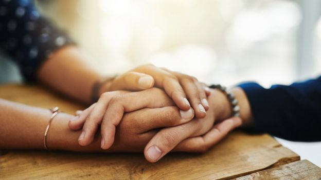 Dos mujeres se toman de la mano.