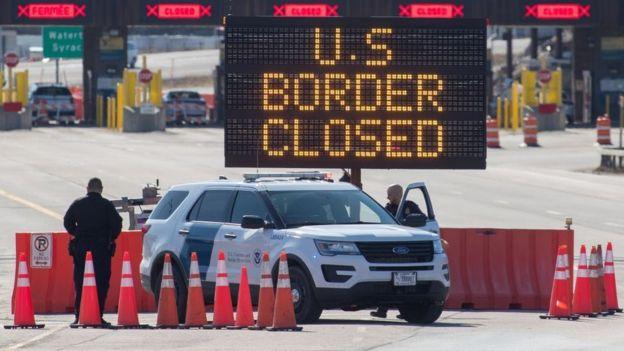 Los funcionarios de aduanas de EE. UU. Junto a un cartel que dice que la frontera de EE. UU. Está cerrada el 22 de marzo de 2020
