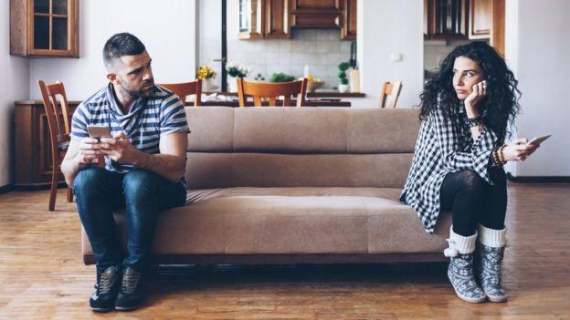 Hombre y mujer en un sofá, cada uno en un extremo