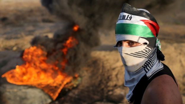 A masked Palestinian protester passes by burning tyres during clashes with Israeli troops near the border between Israel and Central Gaza Strip October 14, 2015.