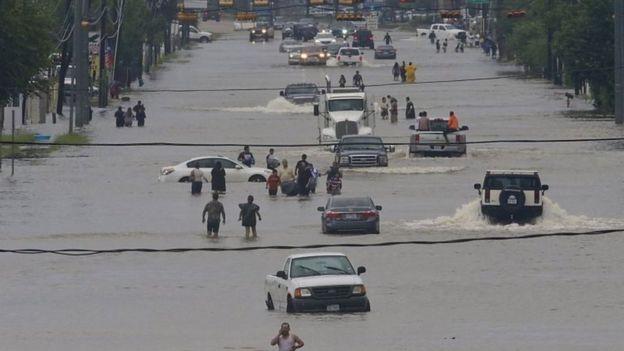 Personas dejan sus autos tras las inundaciones
