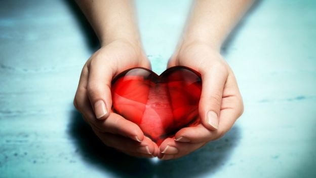 A pair of female hands holding red crystal heart