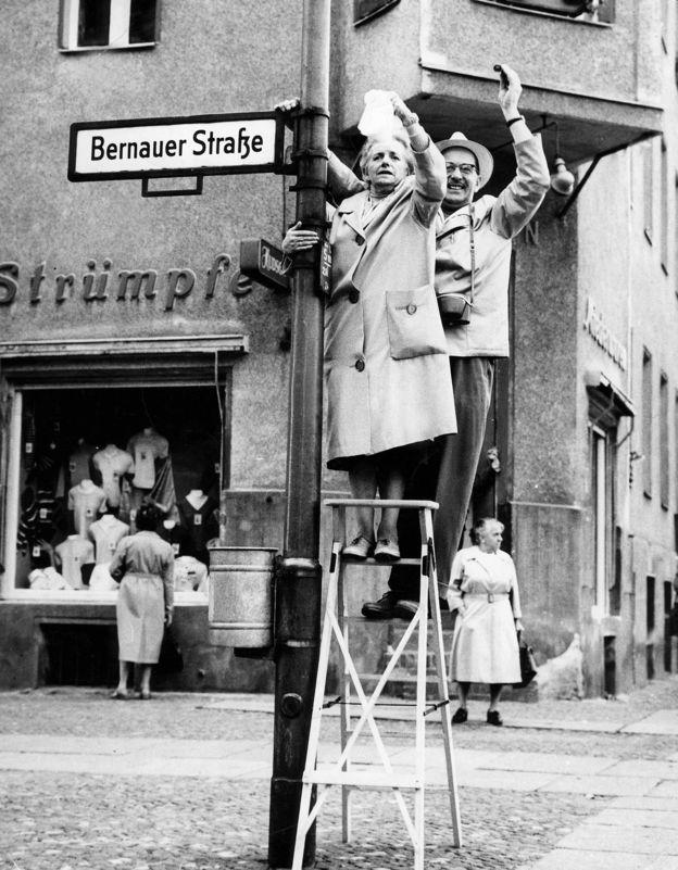 pessoas penduradas numa placa da Bernauer Strasse