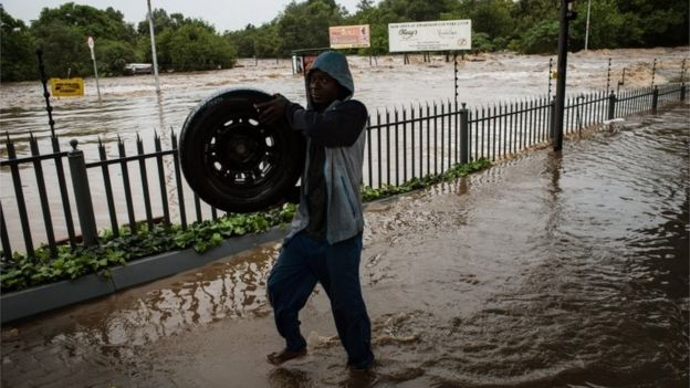 A man working at a car dealership in Centurion retrieves tires floating down river in a flooded area in Centurion, Pretoria, South Africa, 09 December 2011
