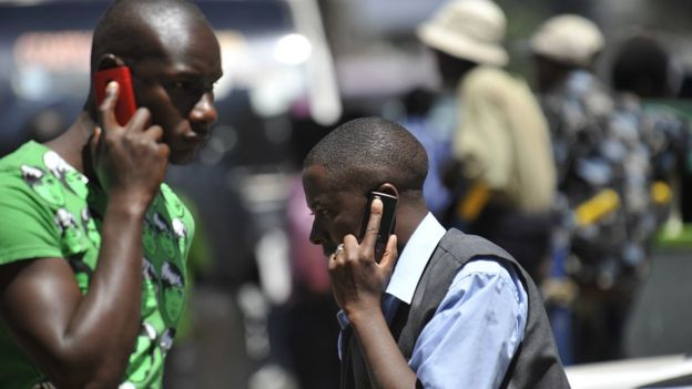 People walk while speaking on the phone on 1 October 2012 in Nairobi, Kenya.