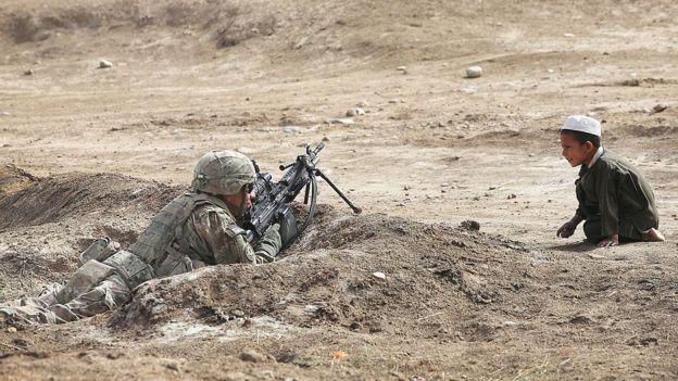 Un niño mira a un soldado del ejército estadounidense en Kandahar, Afganistán en 2014