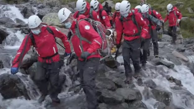 Rescuers carry Daisy across a waterfall