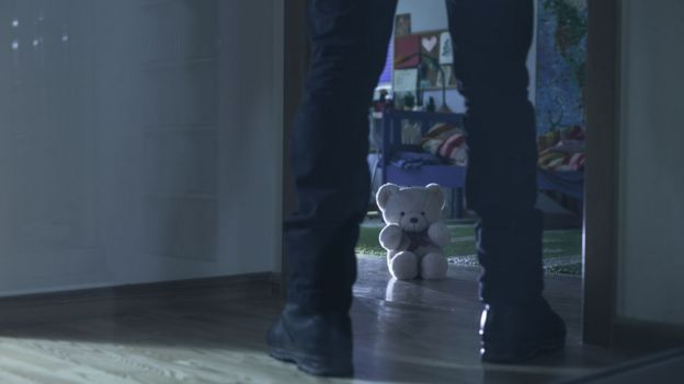 Un hombre amenazante en la entrada de un cuarto infantil.