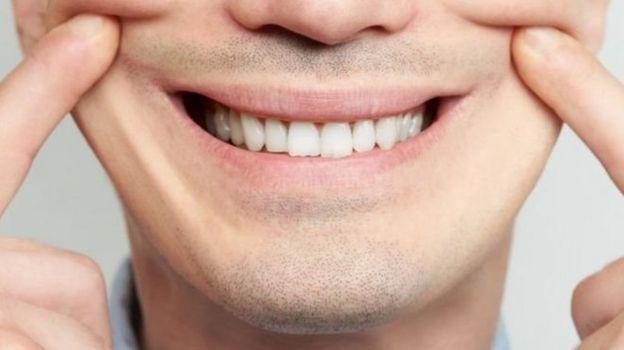 Homem forçando sorriso