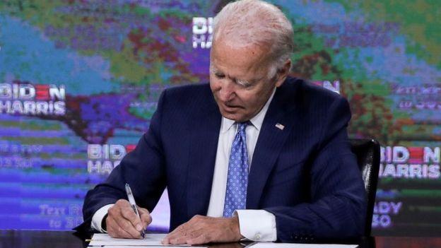 Biden sentado assinando documento