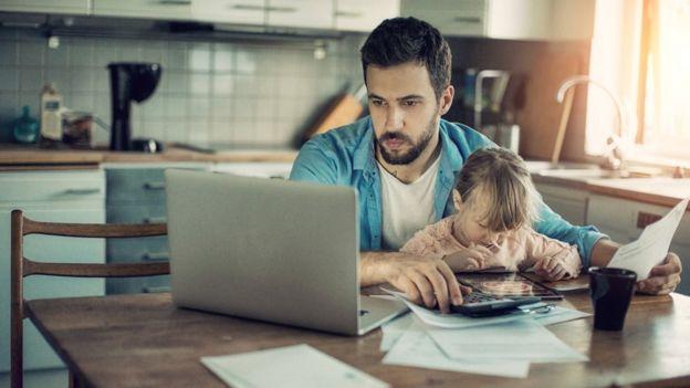 Pai trabalha no computador com a filha no colo
