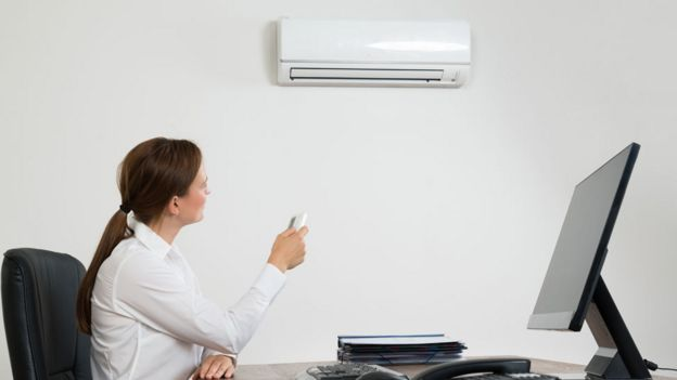 Woman in an office adjusting the air conditioner with a remote control