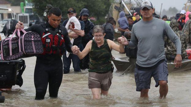 Una mujer recibe ayuda para llegar a tierra después de que su casa quedara inundada en Houston, Texas.