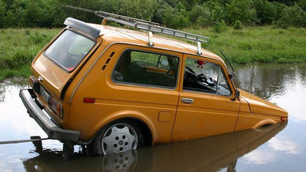 Auto amarillo sumergiéndose en el agua.