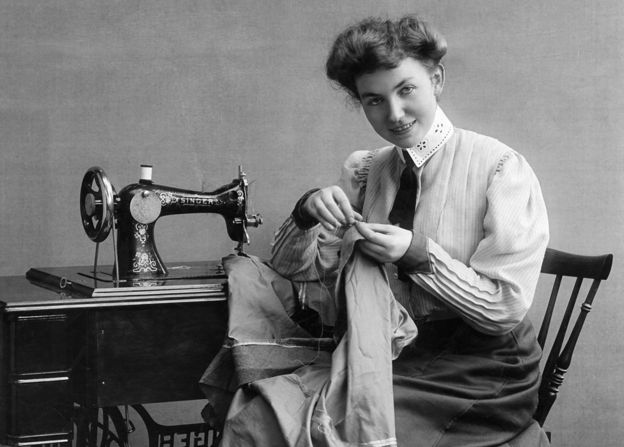 A seamstress using a Singer sewing machine in 1907