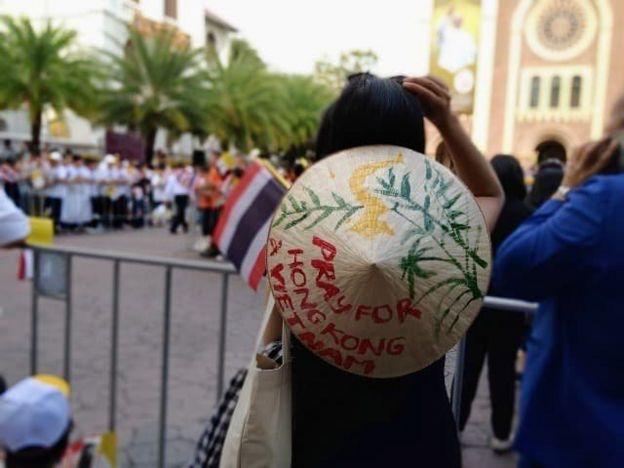 Một bạn trẻ người Việt mang theo chiếc nón có dòng chữ 'Cầu nguyện cho Hongkong và Việt Nam'