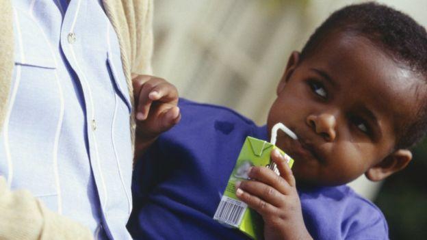 Garotinho tomando suco de caixinha
