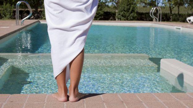 Mujer con una toalla frente a una piscina.