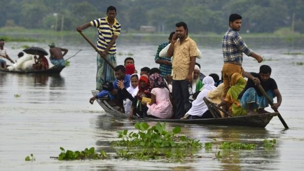 People sit in a boat amid floods in Assam, India