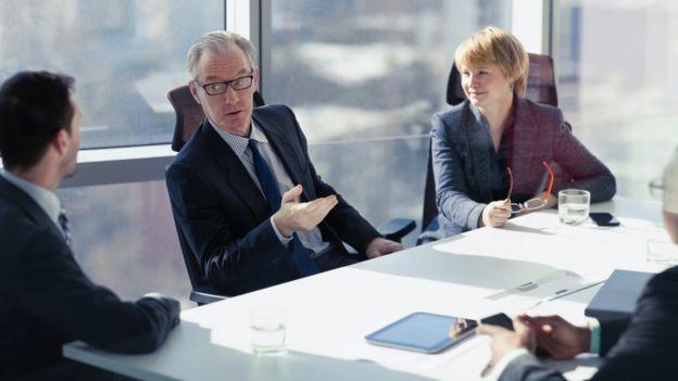 Em encontro de administradores, dois homens conversam enquanto mulher os observa da ponta da mesa www.aquitemtrabalho.com.br