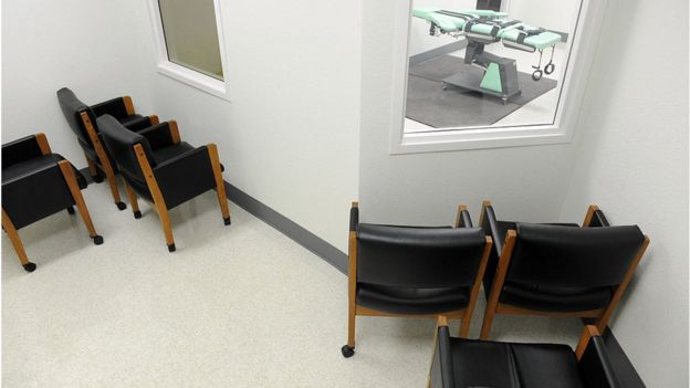Chairs facing a window into the execution room
