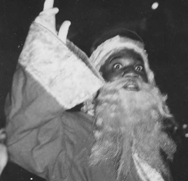 the entertainer bojangles in a santa claus costume waving to a crowd 1937