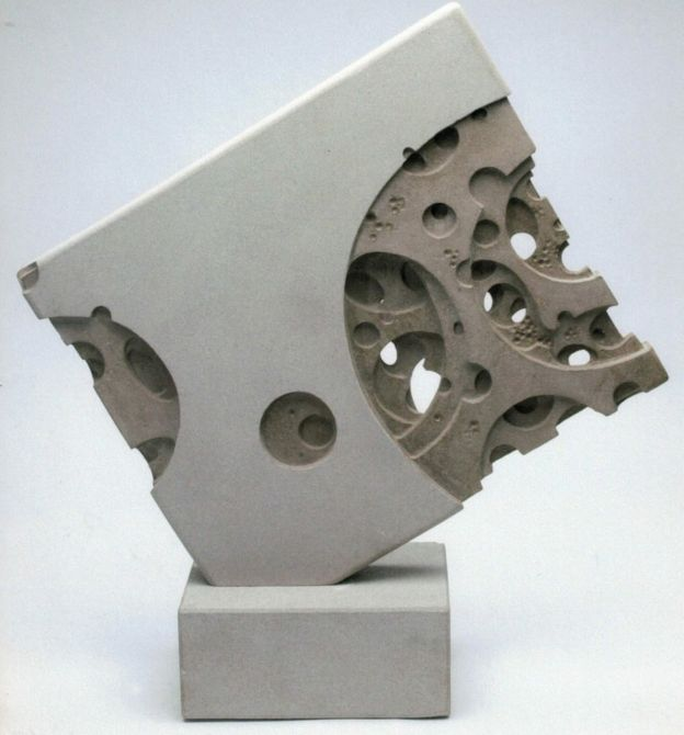 A sculpture of a block with many holes in it