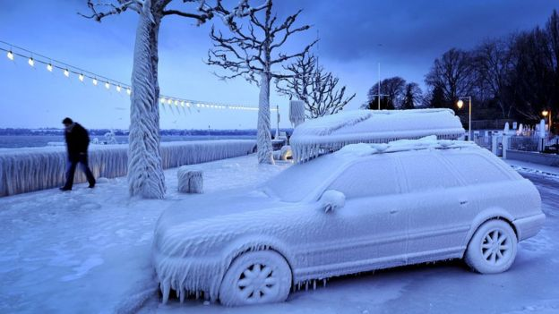 This file photo taken on 5 February 2012 shows a man walking past an ice covered car on the frozen waterside promenade at Lake Geneva in the city Versoix, near Geneva