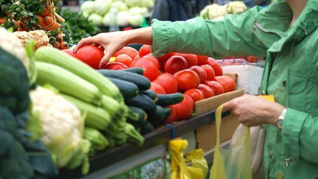 امرأة تشتري فاكهة وخضروات