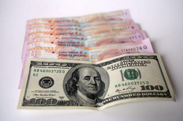 Billete de 100 dólares y de 100 pesos argentinos