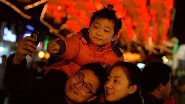 A Chinese family poses for a photo in front of Lantern Festival decorations in Shanghai