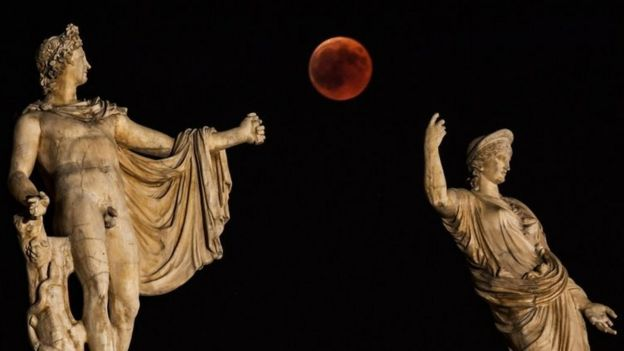 The blood moon beside a statue of ancient Greek goddess Hera and god Apollo in Athens