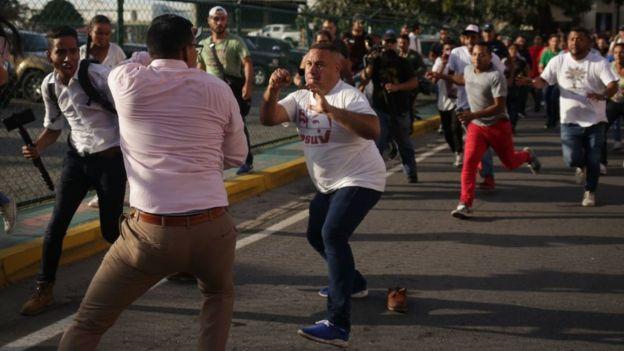 Un partidario de Maduro (centro) confronta a un periodista (segundo a la izquierda) tras la llegada de Guaidó al estado de Vargas.