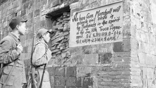 গৃহযুদ্ধ বন্ধে জে মার্শালের চেষ্টার পক্ষে ইংরেজি এবং চীনা ভাষায় পোস্টার পড়ছেন দুজন সৈন্য