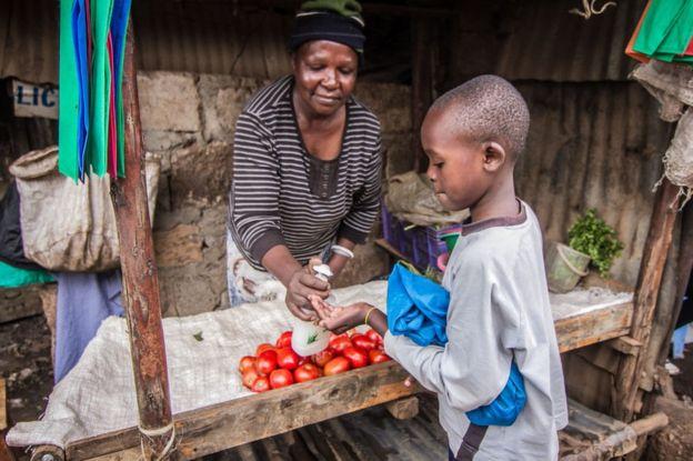 Mulher passa álcool gel em mão de menino em Kibera, no Quênia