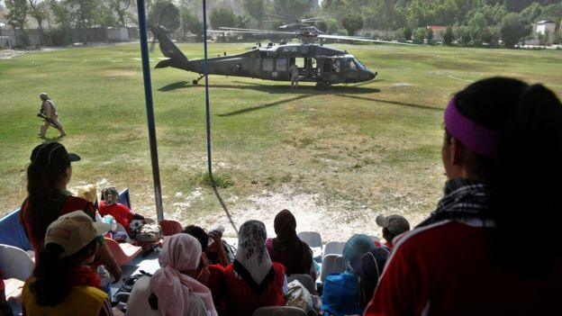 Afghanistan's women's national football team members take a break from training as a US Black Hawk helicopter lands on the pitch at a military club in Kabul on June 20, 2010.