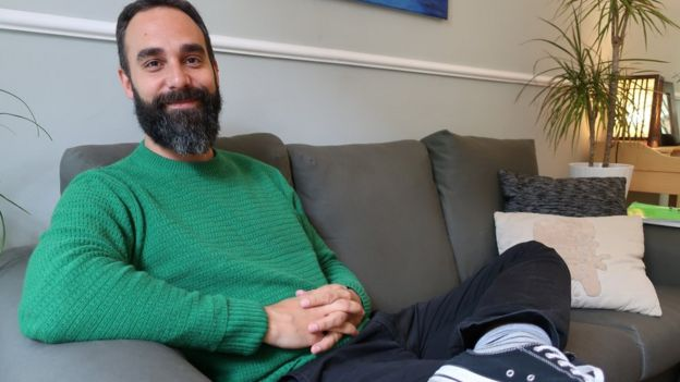 Rafael García is photographed on a couch in a living room