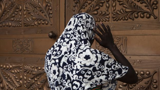 Woman stands outside mosque entrance