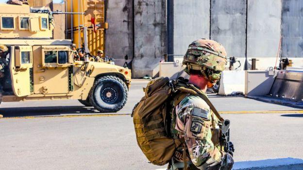 Soldado americano aparece de perfil, na rua, ao lado de tanque