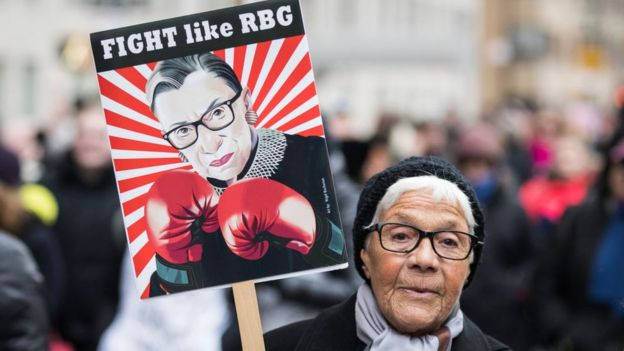 A woman brandishes a sign with Ruth Bader Ginsburg's likeness on it