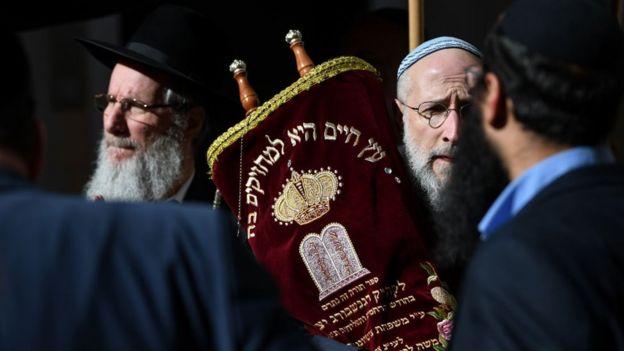 Un hombre sostiene una Torá durante una ceremonia en el patio de la nueva Sinagoga de Regensburg durante su inauguración el 27 de febrero de 2019