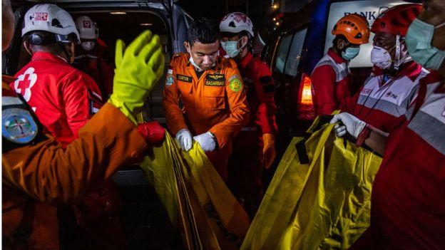 """Индонезийские спасатели и сотрудники Красного Креста переносят тела в машину """"скорой помощи"""" после катастрофы самолета компании Lion Air flight JT 610 в ноябре 2018 года"""