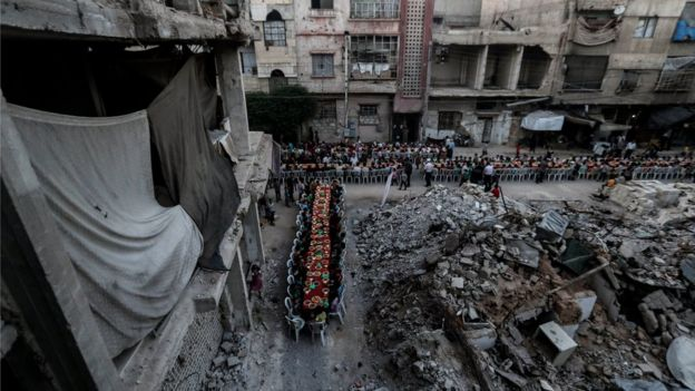 People wait for Iftar, evening meal at the end of daily Ramadan fast at sunset, next to rubble and destroyed houses, which were damaged after air strikes, in Douma, Syria, 17 June 2017.