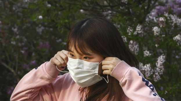Woman putting face mask