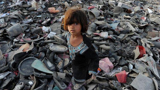 Menina afegã procura objetos em meio a entulho na periferia de Cabul