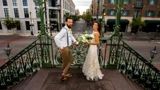 A newlywed couple stand in the deserted streets of Charleston, South Carolina